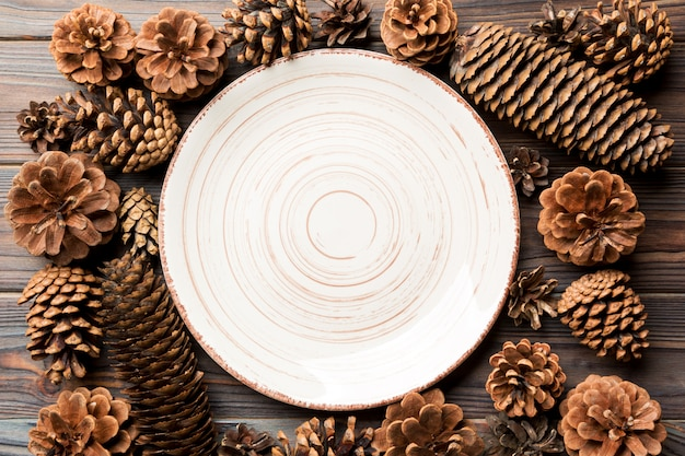 Top view of festive plate with pine cones on wooden surface.