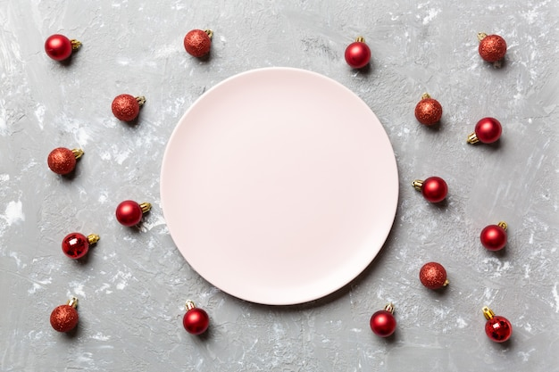 Top view of festive plate with red baubles on cement