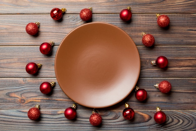 Top view of festive plate with red baubles on wooden background. christmas decorations and toys. new year advent