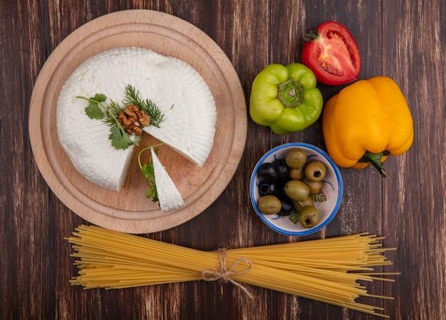 Вид сверху сыр фета на подставке с болгарским перцем, помидорами, оливками и сырыми спагетти на деревянном фоне