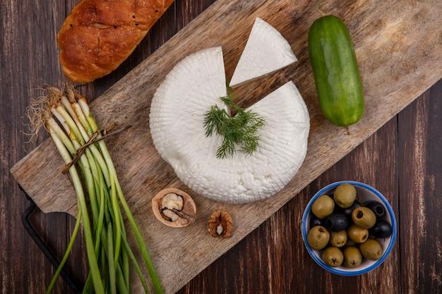 Vista dall'alto di formaggio feta con cetriolo e cipolle verdi su un supporto con olive su uno sfondo di legno
