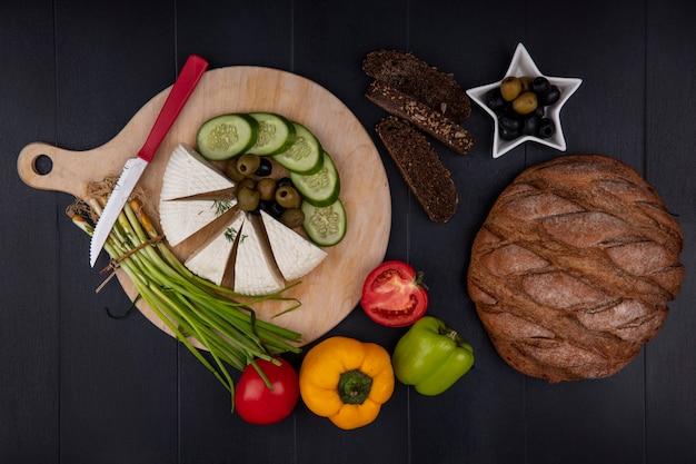 Vista dall'alto di formaggio feta con olive cetriolo cipolle verdi peperoni con un coltello su un supporto e pane nero su sfondo nero