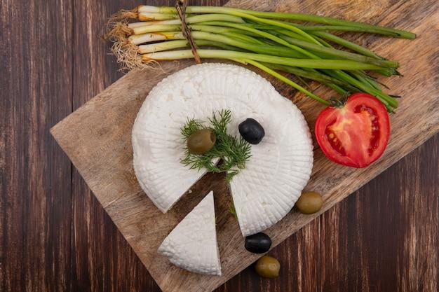 Vista dall'alto di formaggio feta con olive, pomodoro e cipolle verdi su un supporto su uno sfondo di legno