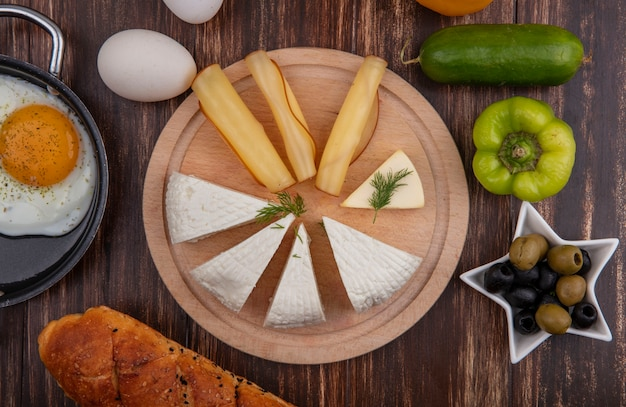 Вид сверху сыр фета с копченым сыром на подставке с оливками, зеленым перцем, огурцом и яйцами на деревянном фоне