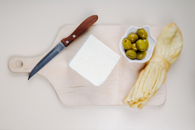 Top view of feta cheese with string cheese , pickled olives and kitchen knife on a wooden cutting board on white table