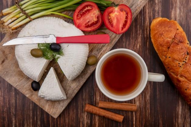 Вид сверху сыр фета с помидорами, оливками и зеленым луком на подставке с чашкой чая и буханкой хлеба на деревянном фоне