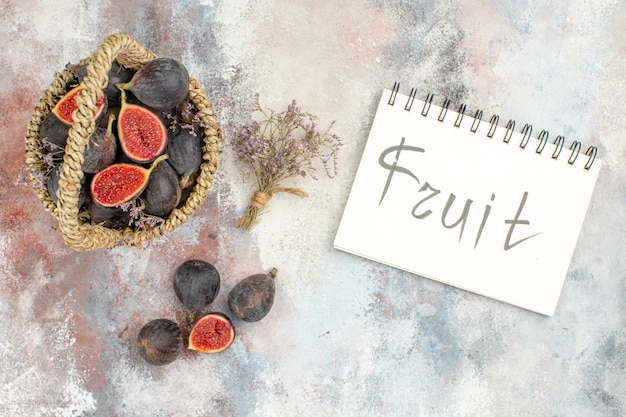 Top view fig basket figs dried flower bunch fruit written on notebook on grey background