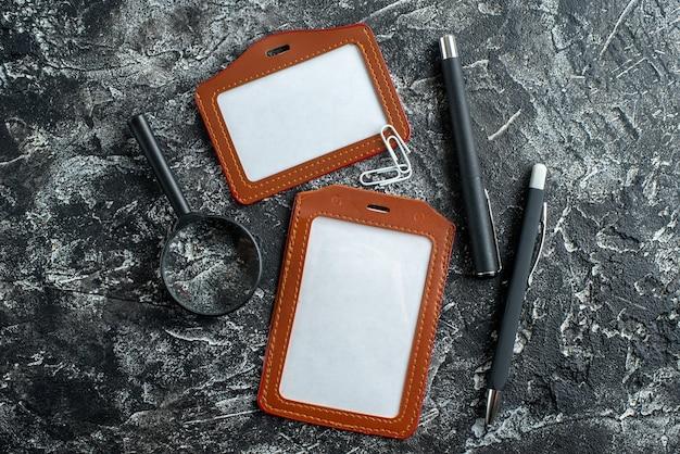 Vista dall'alto di note di file, penne e lente d'ingrandimento sulla superficie di marmo