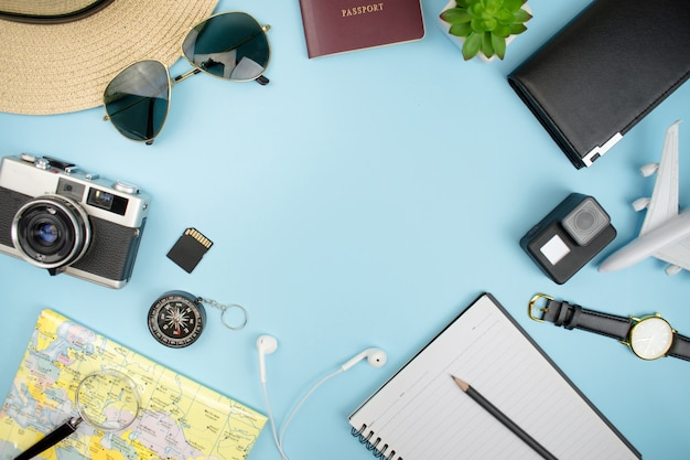 Top view, film camera, map, passport, smartphone, compass, sunglasses, notebook, purse with copy space.