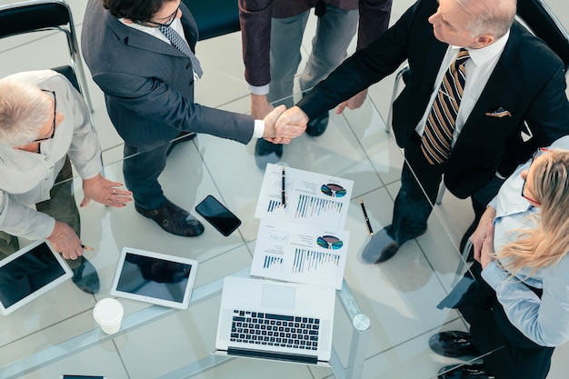 Top view. financial partners confirming the transaction with a handshake