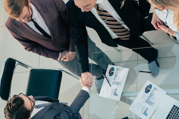 Вид сверху финансовых партнеров, пожимающих руки за столом переговоров