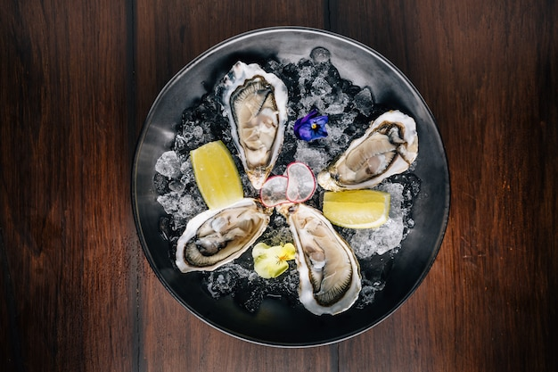 Top view of fine de claire oyster and lemon served in black bowl with ice on wooden table.