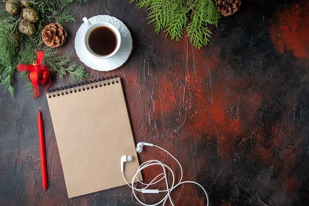 Vista dall'alto dei rami di abete una tazza di accessori per la decorazione del tè nero cuffie bianche e regalo accanto al taccuino con penna su sfondo scuro