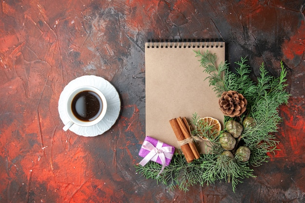 Vista dall'alto di rami di abete regalo di colore viola e quaderno a spirale chiuso lime alla cannella e una tazza di tè nero sul lato sinistro su sfondo rosso