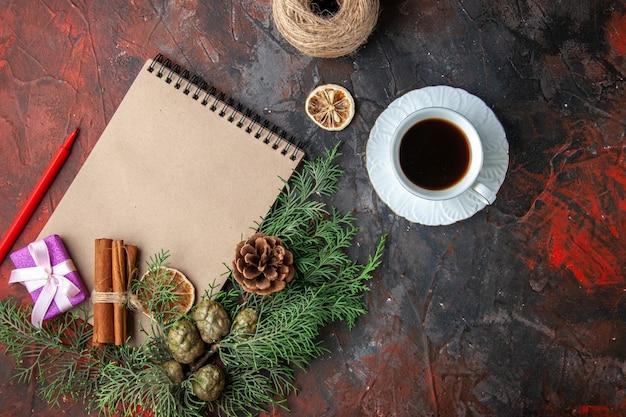 Vista dall'alto di rami di abete regalo di colore viola e quaderno a spirale chiuso lime alla cannella una tazza di tè nero su sfondo rosso