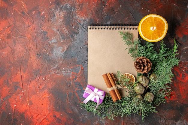 Vista dall'alto di rami di abete regalo di colore viola e quaderno a spirale chiuso lime alla cannella e arancione tagliato sul lato sinistro su sfondo rosso