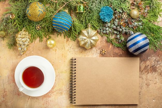 上面図モミの枝のクリスマスツリーはベージュの背景にお茶のノートブックのカップを飾ります