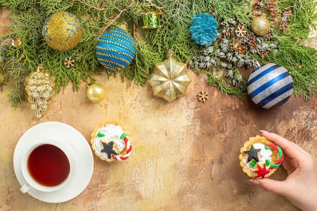 Vista dall'alto rami di abete albero di natale ornamenti una tazza di tè cupcake in mano femminile su sfondo beige