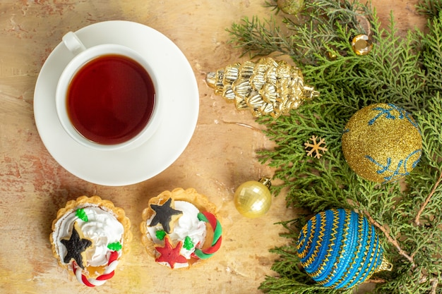 Vista dall'alto rami di abete albero di natale ornamenti cupcakes una tazza di tè su sfondo beige
