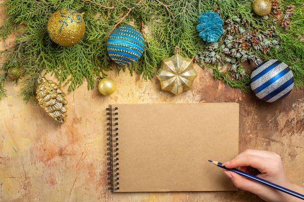 상위 뷰 전나무 가지 크리스마스 트리 장식품 베이지색 배경에 여자 손에 노트북 펜