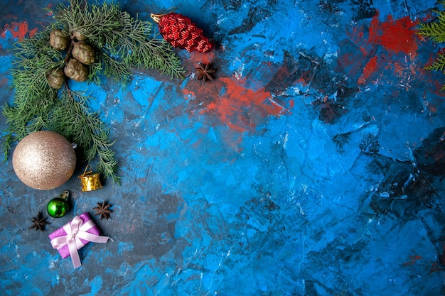 Top view fir tree branches cones xmas tree toys on blue background