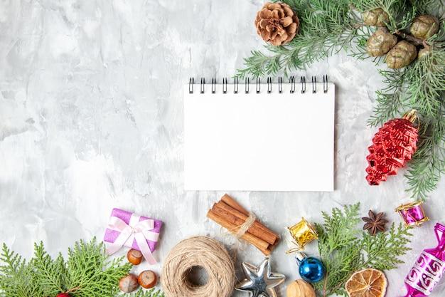 상위 뷰 전나무 나뭇가지 콘 크리스마스 트리 장난감 계피 스틱 아니스 노트북 회색 배경