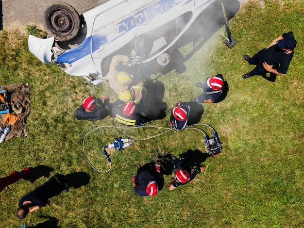 Top view of firefighters trying to release man in the crashed car.