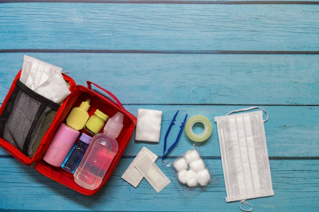 Top view first aid bag kid with medical supplies on wood