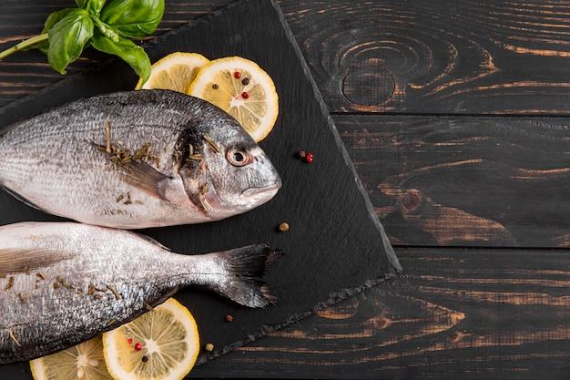 木製の背景に魚とレモンの上面図
