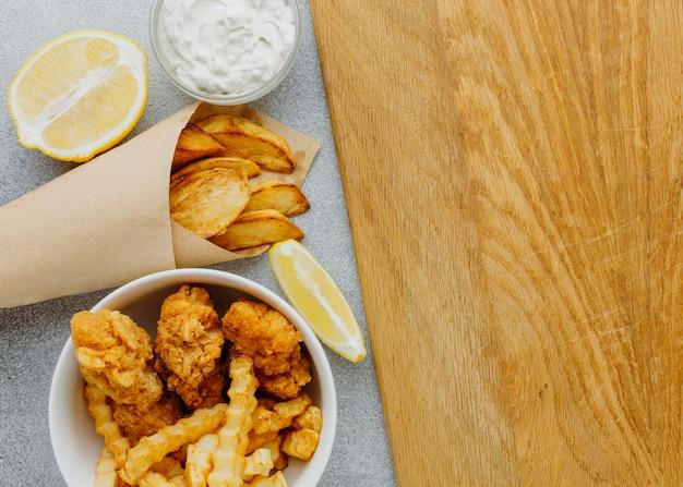 Vista dall'alto di pesce e patatine fritte nella ciotola e involucro di carta con spazio di copia e limone