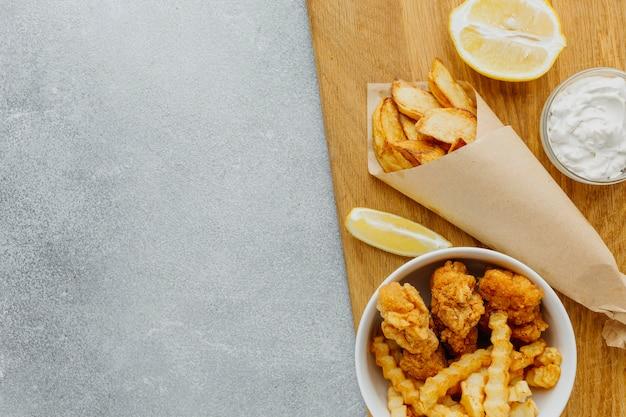 Vista dall'alto di pesce e patatine fritte in ciotola e involucro di carta con lo spazio della copia