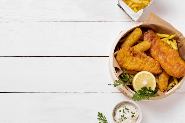 Top view of fish and chips in bowl with lemon