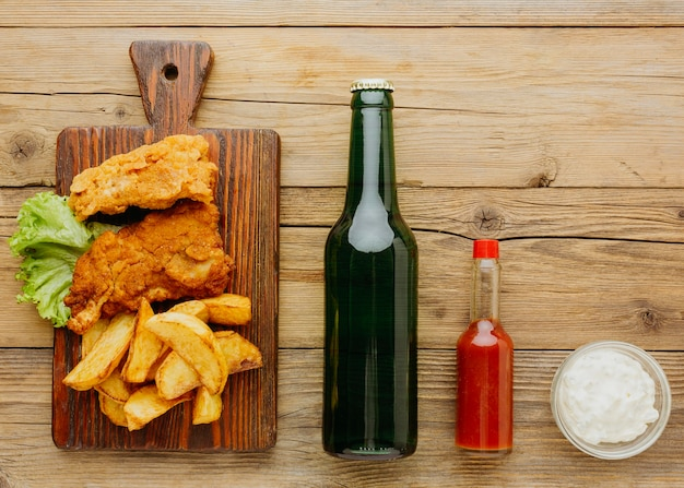 Top view of fish and chips on chopping board with beer bottle and ketchup
