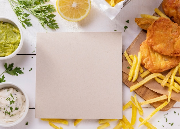 Top view of fish and chips on chopping board with card