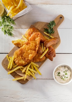 Top view of fish and chips on chopping board with sauce