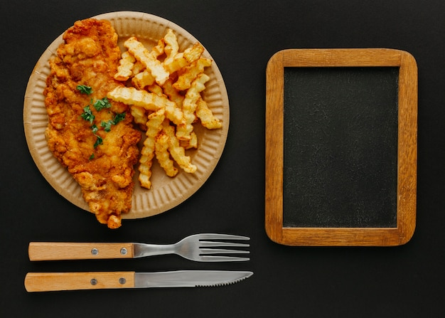 Top view of fish and chips on plate with chalkboard and cutlery