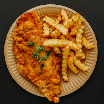 Top view of fish and chips on plate with herbs