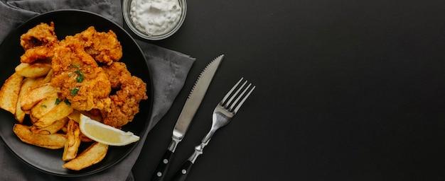 Vista dall'alto di pesce e patatine fritte sulla piastra con fettina di limone e copia spazio