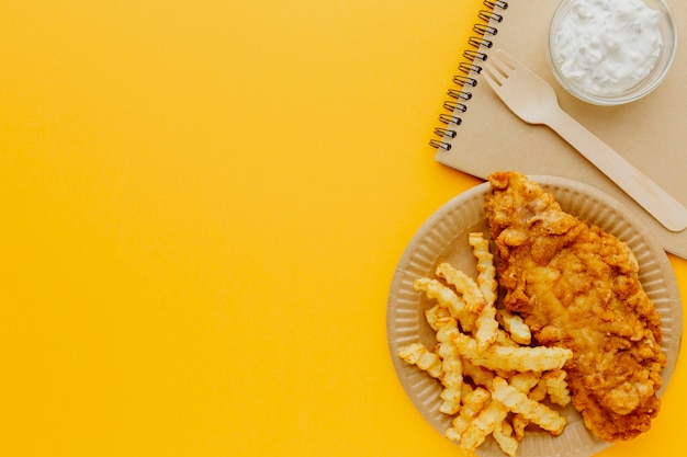 Vista dall'alto di pesce e patatine fritte sulla piastra con il taccuino e la forchetta