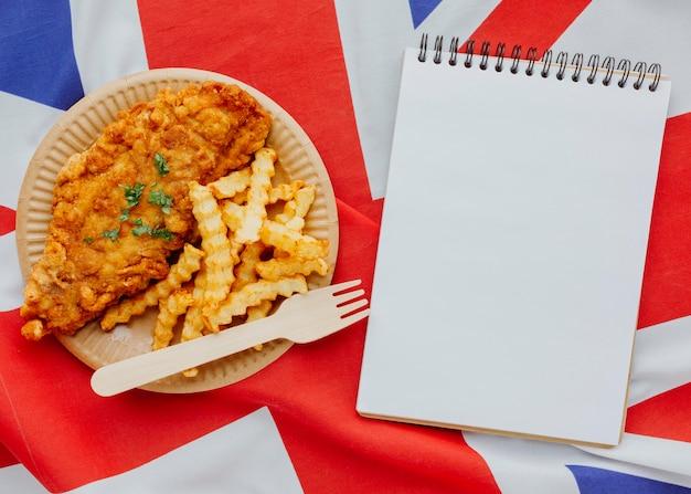 Vista dall'alto di pesce e patatine fritte sulla piastra con il taccuino e la bandiera della gran bretagna