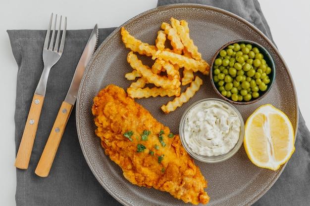 Vista dall'alto di pesce e patatine sulla piastra con piselli e fetta di limone