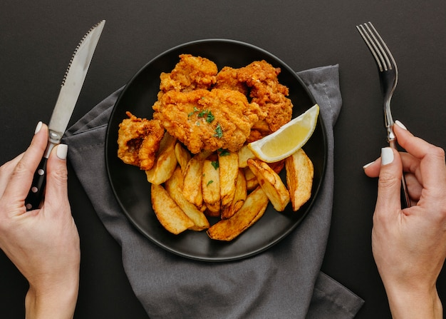 Vista dall'alto di pesce e patatine fritte sulla piastra con la donna che tiene le posate