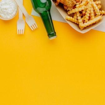 Top view of fish and chips with beer bottle and copy space