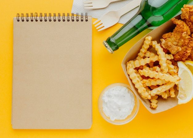 Top view of fish and chips with beer bottle and notebook