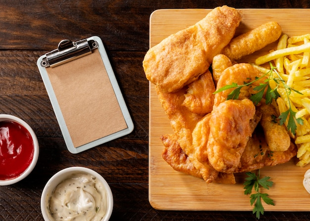 Top view of fish and chips with clipboard and sauces