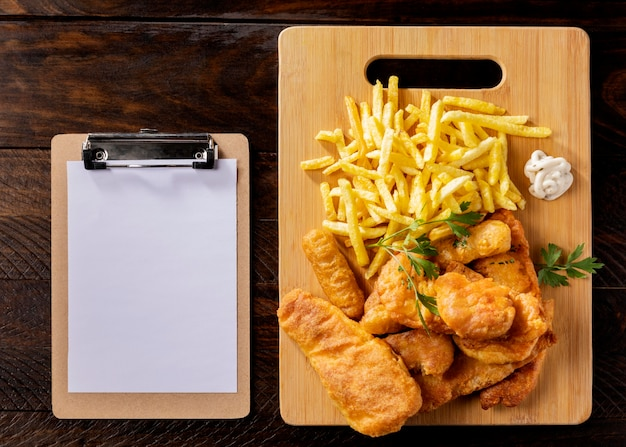 Top view of fish and chips with clipboard