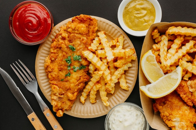 Top view of fish and chips with cutlery and selection of sauces