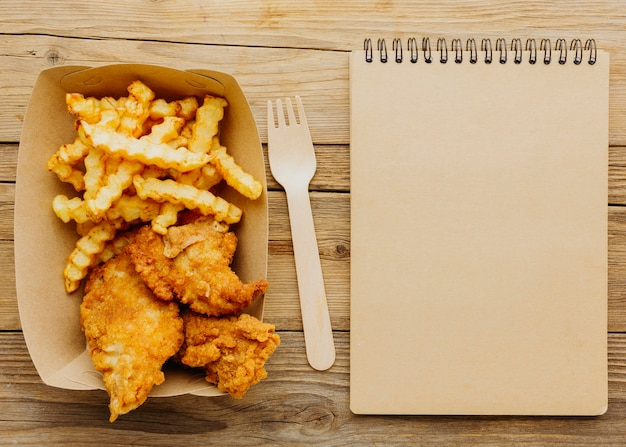 Top view of fish and chips with fork and notebook