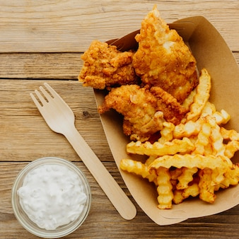 Top view of fish and chips with fork and sauce
