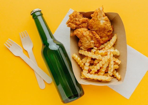Top view of fish and chips with forks and beer bottle